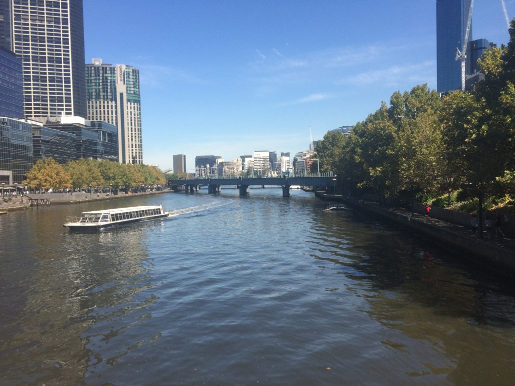 a boat crossing the river in melbourne with skyscrapers in the background